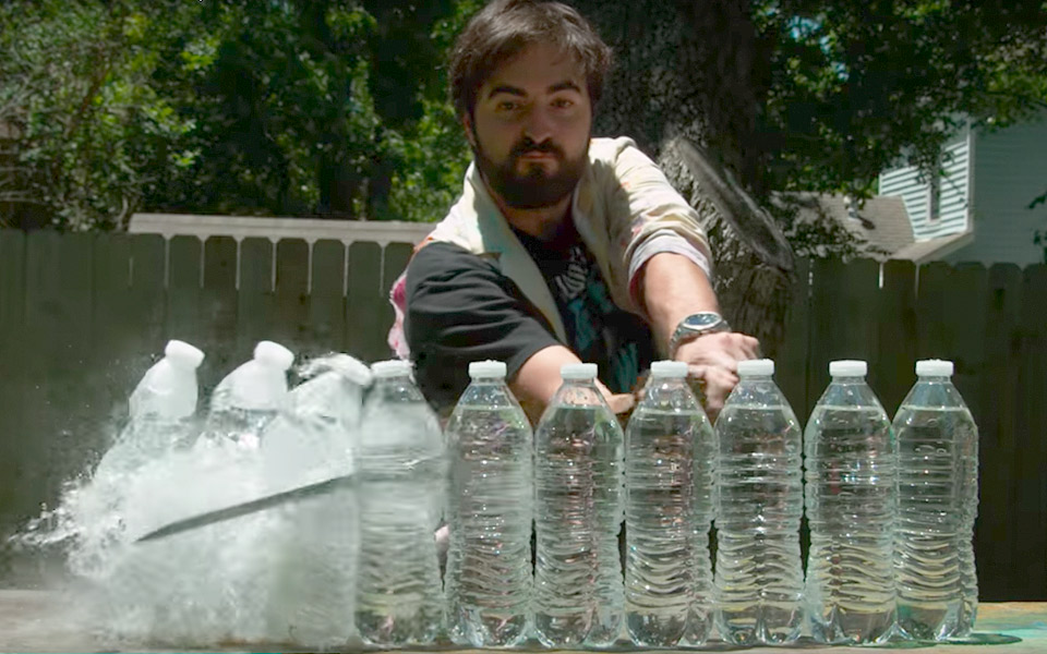 Se et super skarpt samuraisværd skære sig gennem vandflasker i slow motion