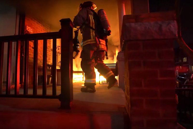 Fyr filmer, mens brandfolk slukker ilden i hans brændende hus